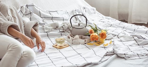 Tee, kekse und ein strauß frischer tulpen im bett. frühstücks- und frühlingsmorgenkonzept.