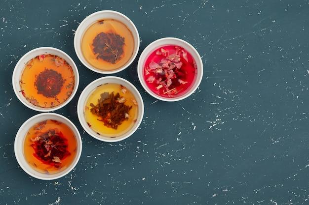 Tee-konzept. verschiedene trockene teesorten in keramikschalen und tassen aromatischen tees