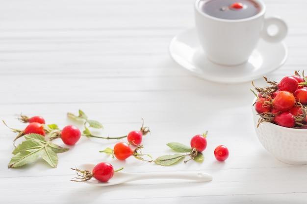 Tee mit beeren einer dogrose auf einem hölzernen hintergrund
