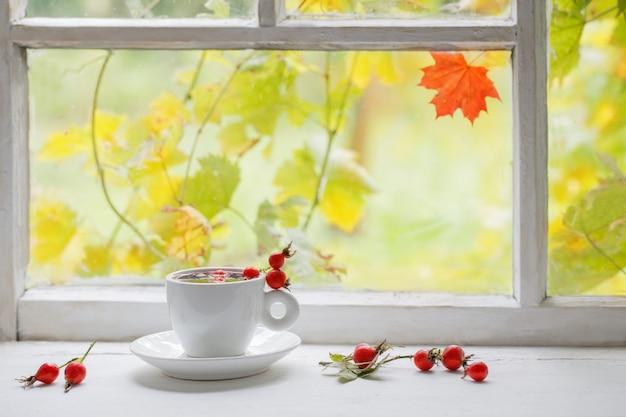 Tee mit beeren einer dogrose auf einer fensterbank