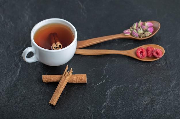 Tee mit blumen und himbeeren auf schwarzem tisch.