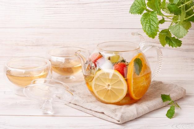 Tee mit früchten und beeren in einer glasteekanne auf weißem holzhintergrund