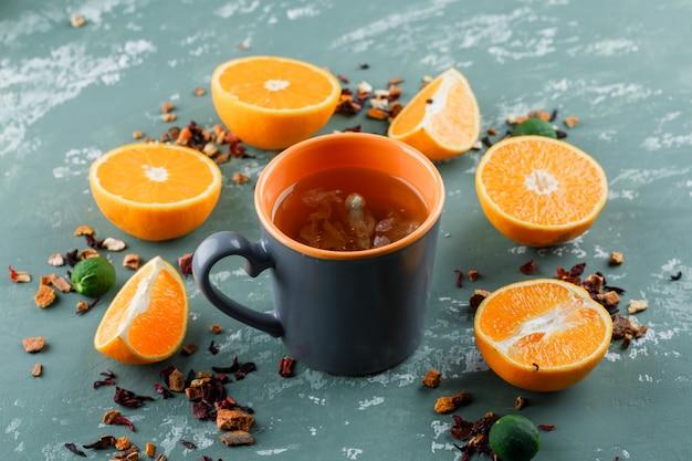 Tee mit gemischten getrockneten kräutern, orangen, limetten in einer tasse auf gipsoberfläche