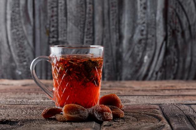 Tee mit getrockneten früchten in einer tasse auf steinfliesen und holzoberfläche