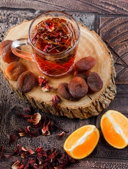 Tee mit getrockneten früchten, kräutern, orange, holz in einer tasse auf steinfliesenoberfläche