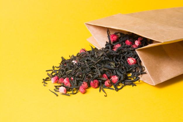 Tee mit getrockneter strohpflanze im gelben hintergrund der papiertüte