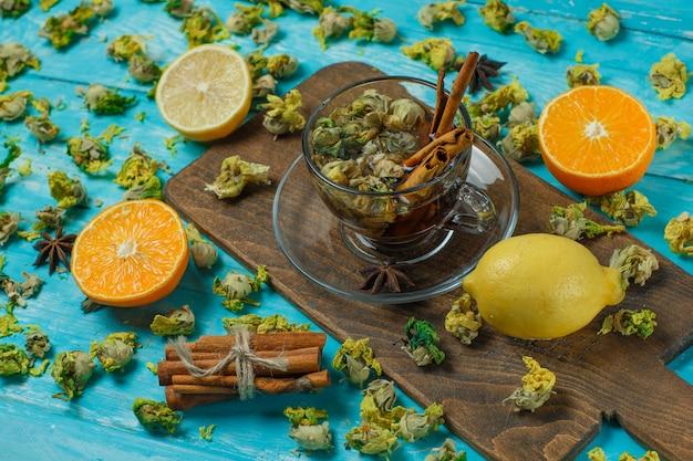 Tee mit gewürzen, orange, zitrone, getrockneten kräutern in einem becher auf blau und schneidebrett