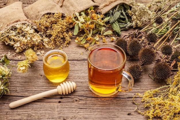 Tee mit honig. kräutererntesammlung und blumensträuße von wildkräutern. alternative medizin. natürliche apotheke, self-care-konzept