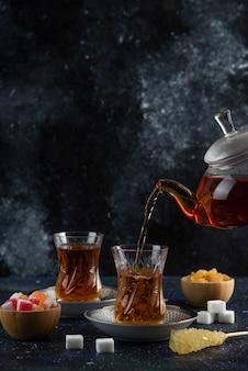 Tee mit köstlichkeiten auf bunter oberfläche