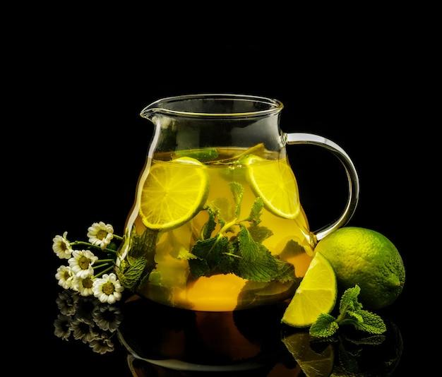 Tee mit limette und minze in einem krug auf einem schwarzen