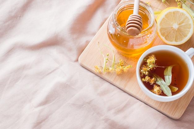 Tee mit linden, honig und zitrone. das tablett auf dem bett, das konzept der behandlung von erkältungen