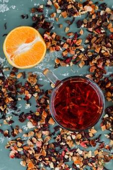 Tee mit orangefarbenen, getrockneten kräutermischungen in einer tasse auf gipsoberfläche