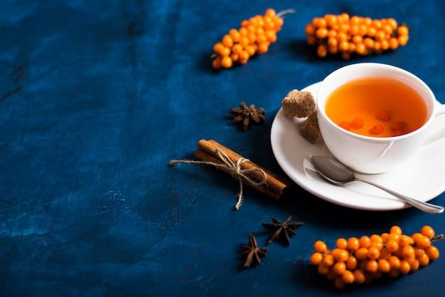 Tee mit sanddorn auf einer dunklen oberfläche