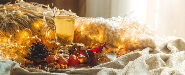 Tee mit sanddornbeeren und ingwer auf alten büchern, honig, kerze und herbstlaub. die atmosphäre des wohlbefindens zu hause. warmes gemütliches zuhause.