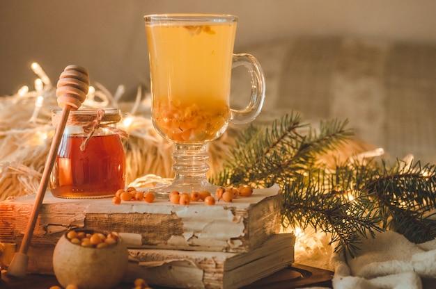 Tee mit sanddornbeeren und ingwer auf alten büchern, honig-, kerzen- und nadelbaumzweigen. die atmosphäre des wohlbefindens zu hause. warmes gemütliches zuhause.