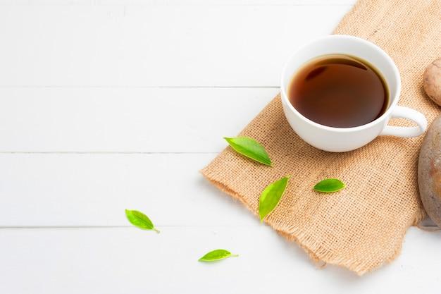 Tee mit teeglas auf weißem holz
