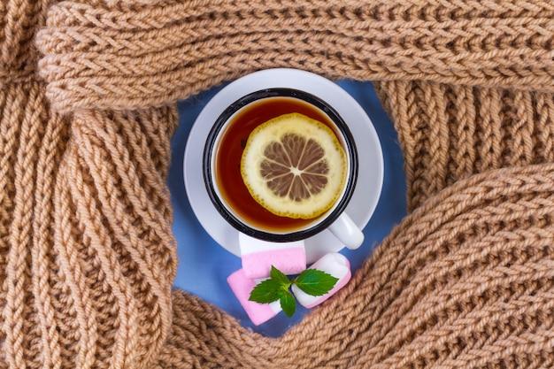 Tee mit zitrone, gestricktem schal, einem stück frischer minze und marshmallows