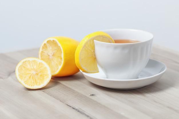 Tee mit zitrone in einer weißen tasse auf einer untertasse auf einer holzoberfläche