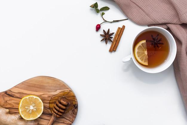 Tee mit zitrone nahe brett mit honigschöpflöffel