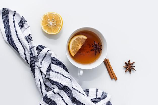 Tee mit zitrone nahe gestreiftem tuch
