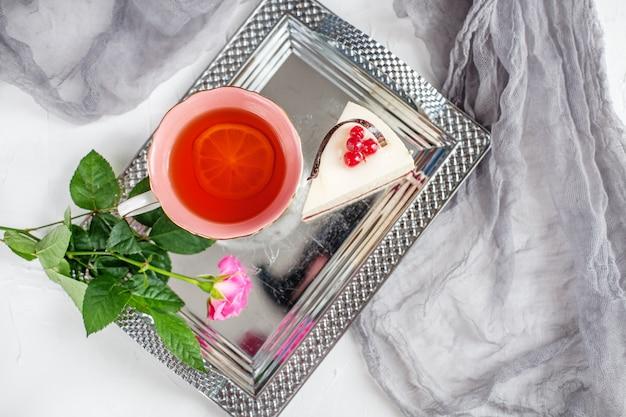 Tee mit zitrone steht auf einem tablett und kuchen. draufsicht das konzept