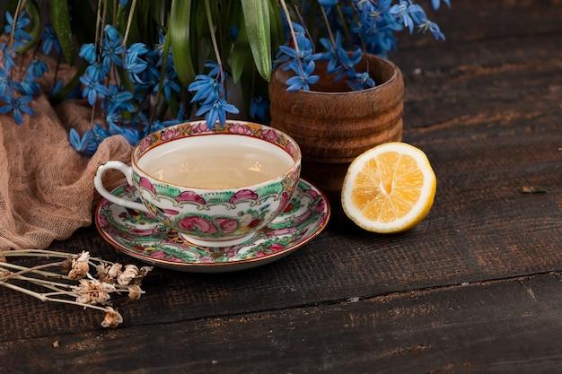 Tee mit zitrone und blumenstrauß von blauen primeln auf dem tisch