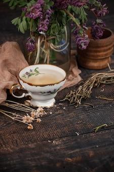 Tee mit zitrone und blumenstrauß von primeln auf dem tisch