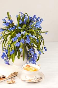 Tee mit zitrone und bouquet von blauen primeln auf dem tisch