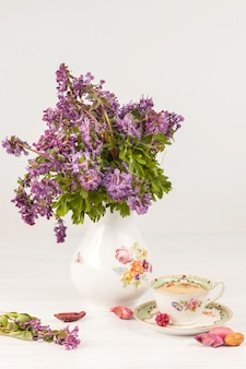 Tee mit zitrone und bouquet von lila primeln auf dem tisch