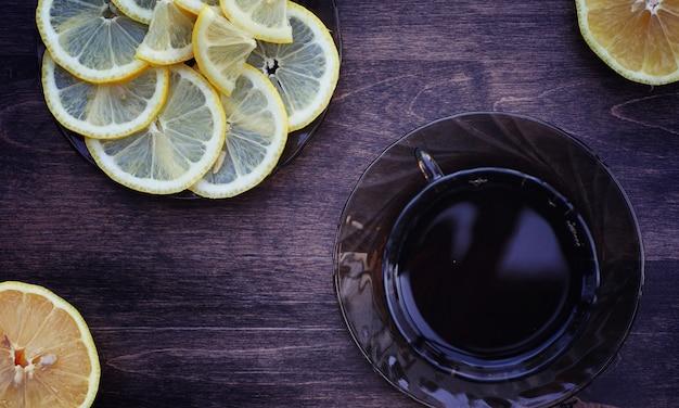 Tee mit zitrone und minze in der natur. eine tasse heißen minztee mit zitrone und honig im glas. zitronenscheiben und ein löffel mit honig zu heißem tee.