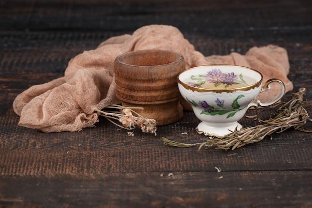 Tee mit zitrone und trockenblumen auf dem tisch