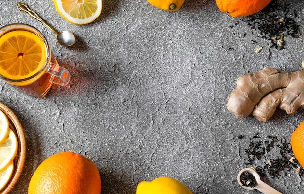 Tee mit zitrusfrüchten (orangen / zitrone) und ingwerwurzelhintergrund.