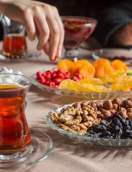 Tee-setup mit schwarzem tee im armudu-glas mit getrockneten furits und nüssen