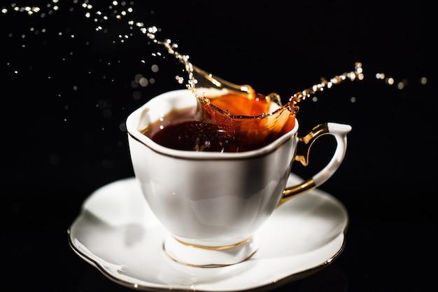 Tee spritzt in der weißen schale auf schwarzem hintergrund