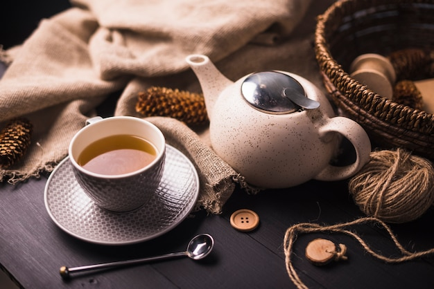 Tee; tannenzapfen; teekanne; taste; sack und weidenkorb auf dem tisch