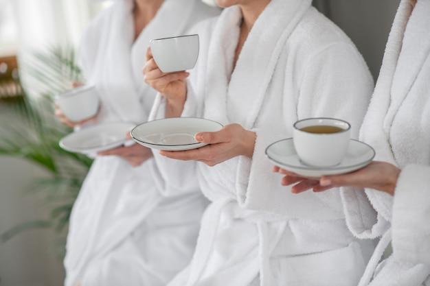 Tee trinken. hände von frauen in weißen bademänteln mit tassen und untertassen, die sich im spa ausruhen, tee trinken, gesichter nicht sichtbar