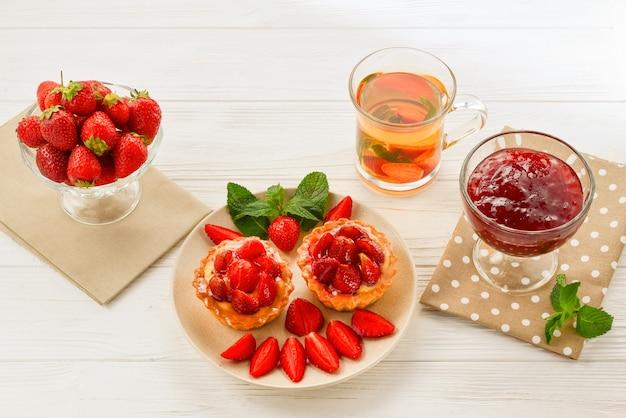 Tee trinken mit törtchen und kuchen mit erdbeeren