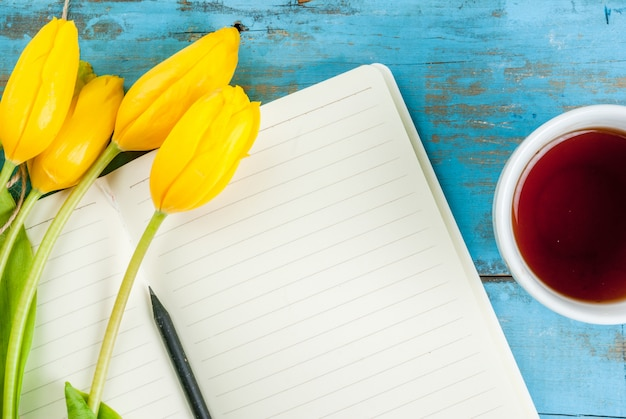 Tee, tulpen und notizbuch auf blauem tisch