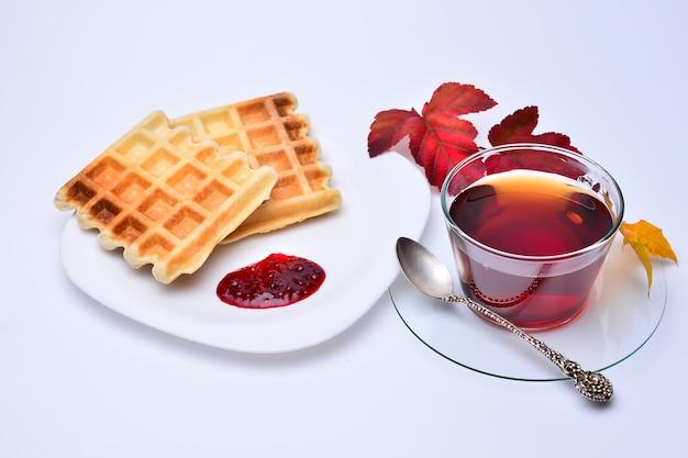 Tee und belgische waffeln getrennt auf dem weiß