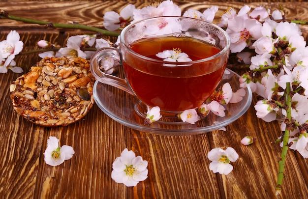 Tee und eine niederlassung von kirschblüten auf einem hölzernen