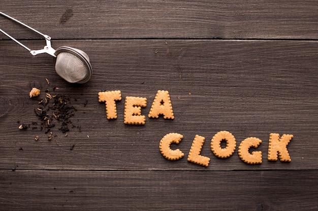 Tee und eine plätzchenaufschrift auf einem holztisch