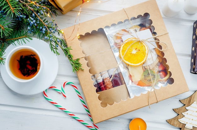 Tee und geschenkbox mit trockenen fruchtchips auf holztisch