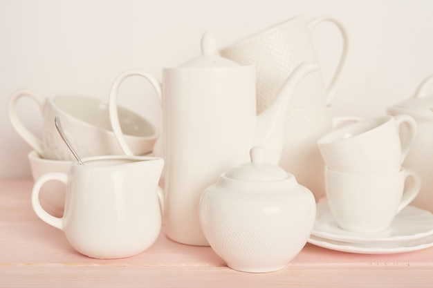 Tee- und kaffeesatz auf dem tisch auf einem weißen hintergrund