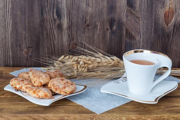 Tee und selbst gemachte plätzchen auf einem hölzernen hintergrund