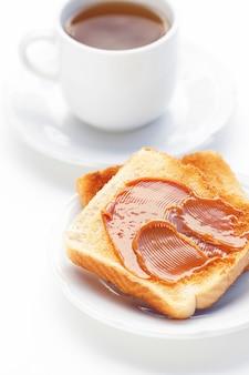 Tee und toast mit dem karamell getrennt auf weiß
