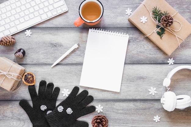 Tee- und wintersymbole nähern sich geräten und notizbuch