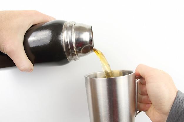 Tee wird in eine tasse thermoskanne gegossen