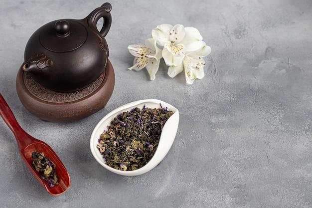 Tee-zeremonie. chinesisches pu-erh in einer schüssel. im hintergrund eine braune teekanne und teeblätter. speicherplatz kopieren.