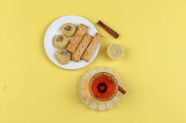 Tee, zitrone, zimtstangen und kekse