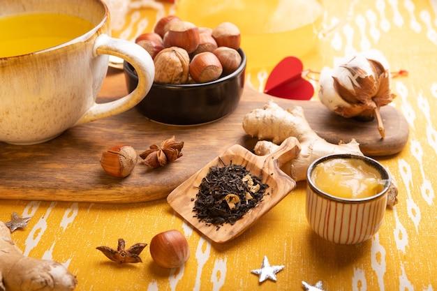 Tee zutaten auf dem tisch trockener tee in holzlöffel, ingwerwurzel und honig.